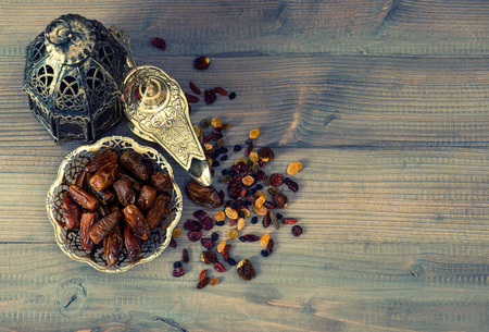Vintage oriental latern, raisins and dates on wooden background. retro style toned picture