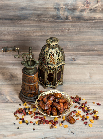 orintal: Still life with vintage orintal latern and mill. Raisins and dates on wooden background