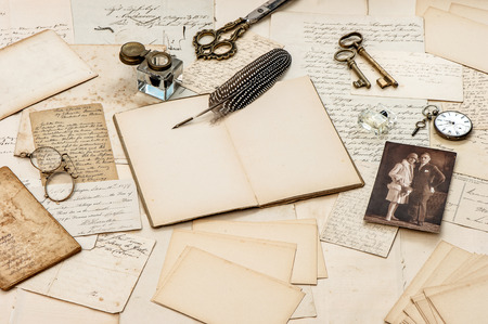 old letters, vintage postcards and antique feather pen. nostalgic sentimental background with retro picture of young couple