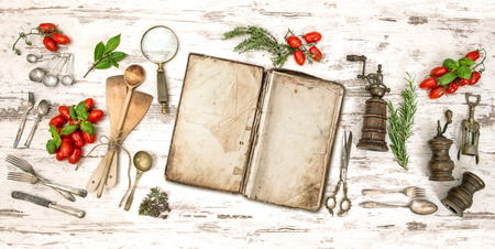 Old cookbook with vegetables, herbs and vintage kitchen utensils. Retro style toned picture photo