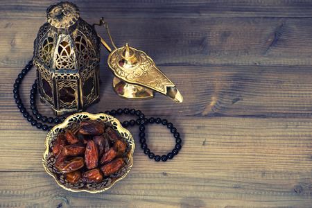 quran: Dates, arabian lantern and rosary. Islamic holidays concept. Ramadan decoration. Retro style toned picture Stock Photo