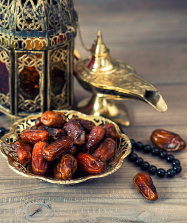 Traditional arabic lamp, latern, dates and rosary. Islamic holidays concept. vintage style toned picture