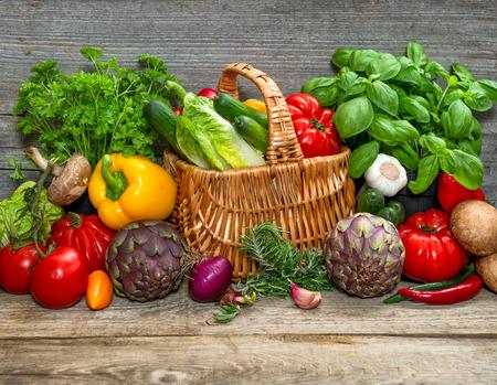 stile country: verdure ed erbe su sfondo di legno. freschi ingredienti alimentari crudi. immagine in stile country. messa a fuoco selettiva