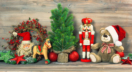 nostalgic christmas decoration with antique toys teddy bear and nutcracker. retro style toned picture photo