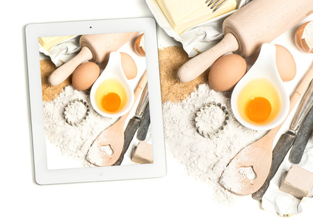 notebook tablet pc and baking ingredients eggs, flour, sugar, butter, yeast. taking food photos with digital tablet pc photo