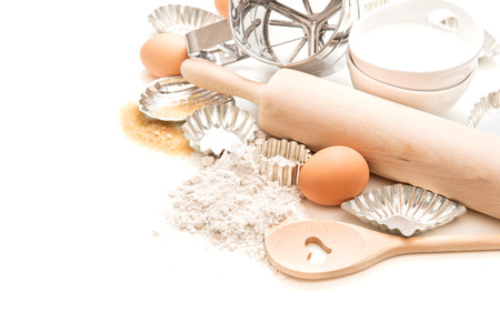 flour, eggs, sugar, rolling pin and cookie cutters on white background. sweet food cooking Banco de Imagens