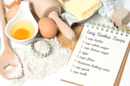 cookies baking ingredients eggs, flour, sugar, butter, yeast. recipe book with sample text photo