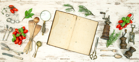 Vintage kitchen utensils with old cookbook, vegetables and herbs. Retro style toned picture photo
