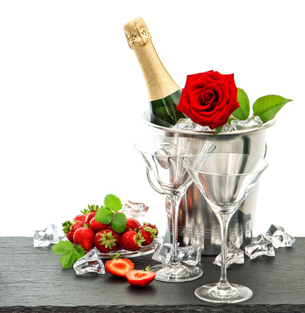 festive arrangement with champagne, red rose and strawberries over white background photo