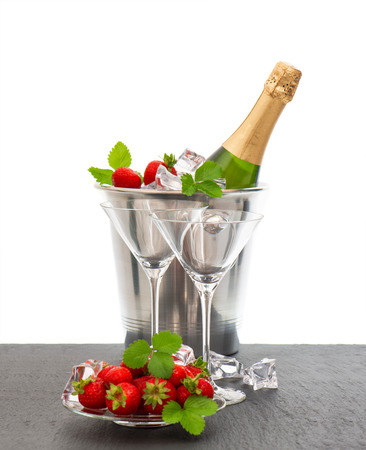 bottle of champagne and two glasses over white background  festive arrangement with sparkling wine and strawberries photo