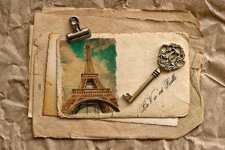 belle: old paper sheets with clip, vintage key and sample text La Vie est Belle