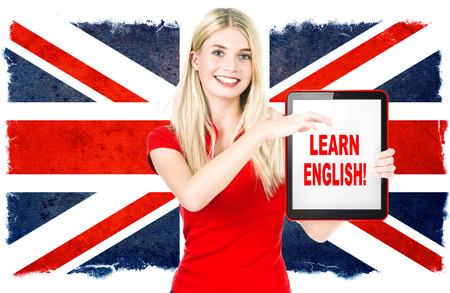 bandera inglaterra: Mujer joven celebración de Tablet PC en el fondo con la bandera nacional británico concepto de aprendizaje Inglés