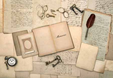 old letters: open book, vintage accessories, old letters, post cards, glasses, keys, clock  nostalgic background  memories