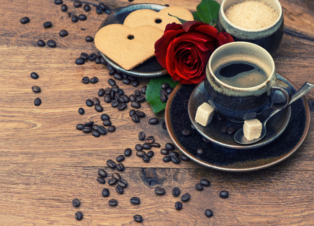Cup of black coffee with red rose flower and heart cake on wooden background  Festive arrangement photo
