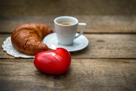bougie coeur: Tasse de caf� noir avec un croissant et bougie rouge de coeur sur fond de bois mise au point s�lective Banque d'images