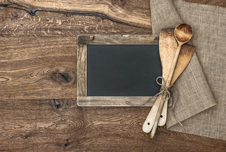 Retro kitchen utensils and vintage blackboard on wooden background photo