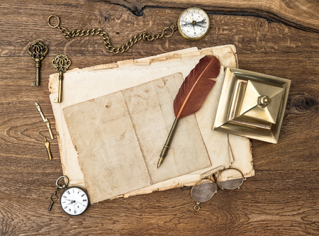 antique accessories and office supplies over wooden table background  vintage keys, clock, glasses, feather pen, compass  nostalgic sentimental picture photo