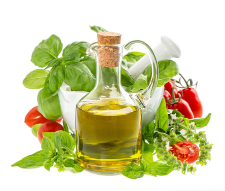 bottle of olive oil with fresh mediterranean herbs and tomatoes isolated on white. food background photo