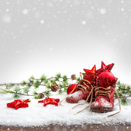 baby christmas: nostalgic christmas decoration with antique baby shoes. festive background. retro style picture with snow effect