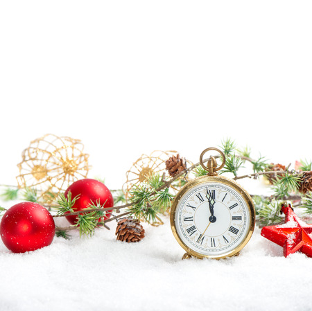 vintage christmas decoration red baubles and antique golden clock in snow on white background photo