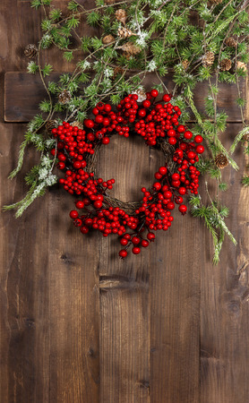 green christmas tree branches and wreath from red berries over rustic wooden background. festive decoration photo