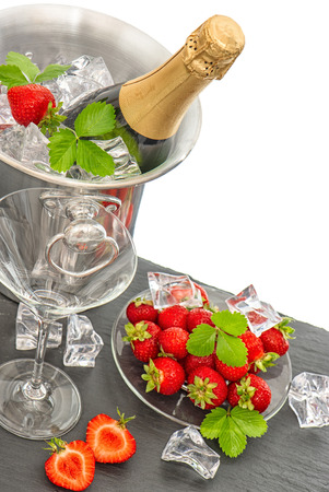 bottle of champagne and two glasses over white background. festive arrangement with sparkling wine and fresh strawberries. top view. selective focus photo