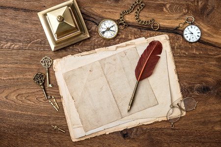 antique accessories and office supplies on wooden table. vintage keys, clock, glasses, feather pen, compass. nostalgic sentimental background photo