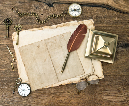 antique office supplies and accessories on wooden table. vintage keys, clock, glasses, feather pen, compass. nostalgic sentimental background photo