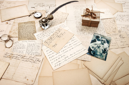 old letters, vintage postcards and antique feather pen. nostalgic sentimental background with retro picture of couple