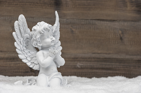 sculptures: little white guardian angel in snow on wooden background. vintage style christmas decoration