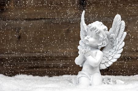 baby angel: piccolo angelo custode bianca di neve su fondo in legno. decorazioni natalizie in stile vintage con effetto fiocchi di neve caduta