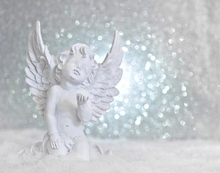 반짝 조명 배경에 눈이 작은 흰색 수호 천사. 크리스마스 장식 스톡 콘텐츠