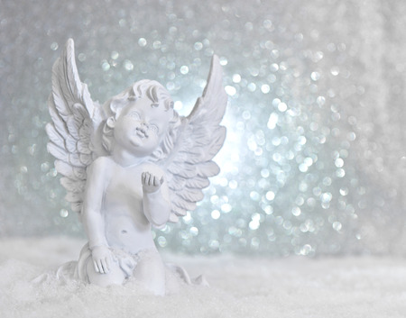 cherub: little white guardian angel in snow on shiny lights background. christmas decoration