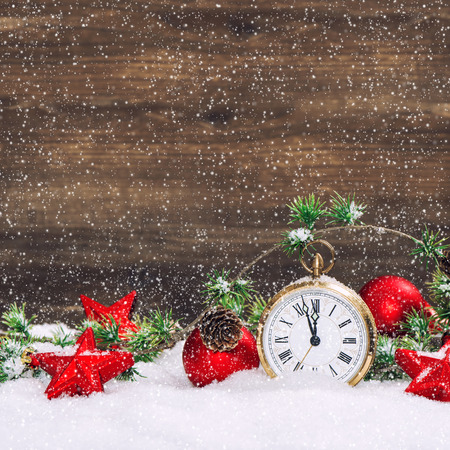 christmas decoration red stars and baubles and antique golden clock in snow over wooden background. vintage style picture with falling snow effect photo