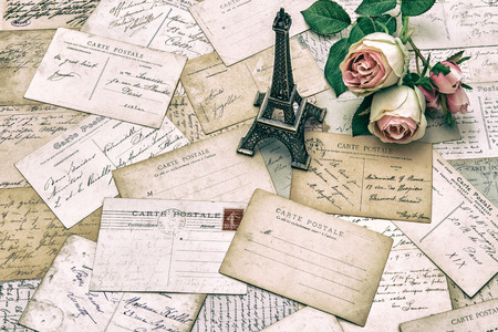 roses, antique french postcards carte postale and souvenir Eiffel Tower from Paris. nostalgic holidays background. retro style toned picture photo