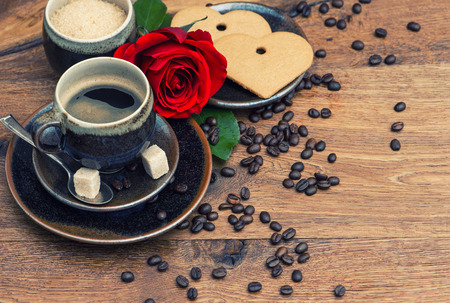 Cup of black coffee with red rose flower and heart cake on wooden background. retro style toned picture photo