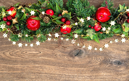 クリスマスの装飾は、木製の背景に赤いリンゴと緑の松の枝ガーランドします。 写真素材