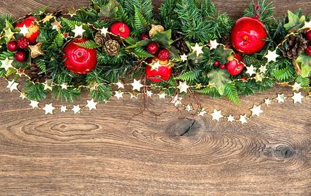 kerstversiering krans met rode appel en groene dennentakken over houten achtergrond Stockfoto