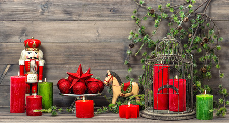 vintage christmas decorations with red candles, antique toys nutcracker and rocking horse. retro style toned picture photo