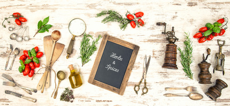 Vintage kitchen utensils with red tomatoes and herbs. Blackboard with sample text Herbs & Spices photo