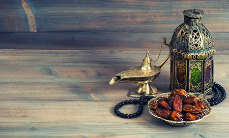Dates, arabian lantern and rosary. Islamic holidays concept. Ramadan decoration. Retro style toned picture Imagens
