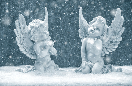 angel statue: little guardian angels in snow on shiny lights background. christmas decoration Stock Photo