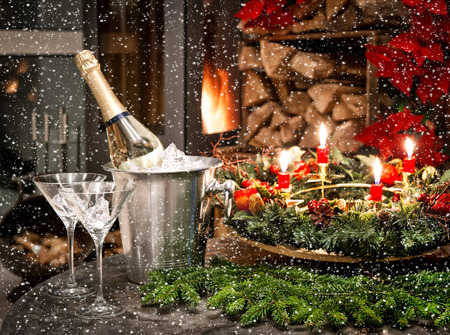 festive home interior decoration for christmas and new year with bottle of champagne and fireplace. candlelight dinner. picture with falling snow effect photo