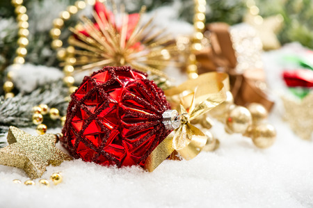 festive christmas decoration with red baubles und golden gift box on white background photo
