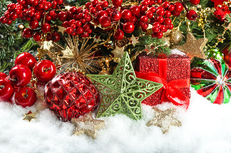 festive decoration with baubles, golden garlands, christmas tree and red berries branches. holidays background photo