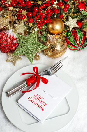 festive table setting decoration with baubles, golden garlands, candle, christmas tree and red berries. dinner invitation concept with sample text Merry Christmas photo