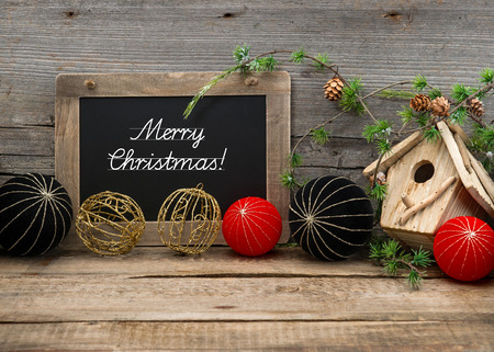 vintage christmas decoration with blackboard for your text over rustic wooden background. red and black china style balls and baubles. sample text Merry Christmas photo