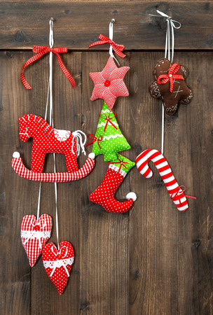 christmas decoration handmade toys hanging over rustic wooden background. nostalgic retro style picture photo