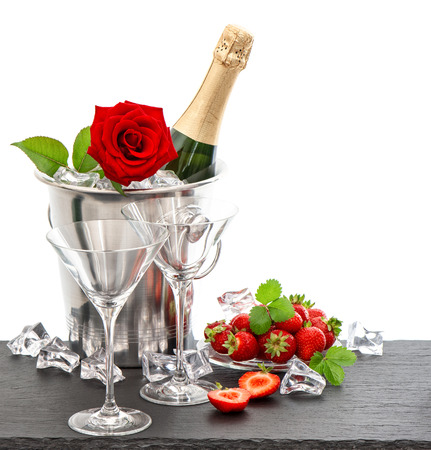 wedding table setting: festive arrangement with champagne, red rose and strawberries over white background Stock Photo