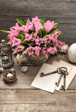 vintage easter decoration with cage, eggs and soft pink tulip flowers. country style picture. selective focus photo